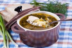 Geschmackvolle Suppe in den Kasserollen mit einem Löffel, Abschluss oben Stockbild