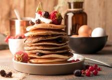 geschmackvolle traditionelle amerikanische Pfannkuchen im Stapel mit Sahne, frischen Beeren auf weißer Platte nahe Schüssel mit r lizenzfreie stockfotos