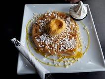 Geschmackvolle Waffel mit Mango-Sorbet und weißer Schokolade stockfotos
