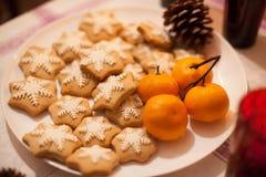 Geschmackvolle Weihnachts-coockies und -mandarinen auf Platte Stockfoto