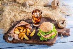 Geschmackvoller Burger mit Fischen diente mit kaltem Getränk Lizenzfreie Stockfotografie