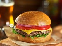 Geschmackvoller Cheeseburger mit Bier im Hintergrund stockbilder