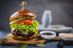 Geschmackvoller gegrillter glasig-glänzender Rindfleischburger mit Kopfsalat und Käse diente Stockbilder