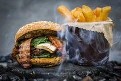 Geschmackvoller geräucherter gegrillter und glasig-glänzender Rindfleischburger mit Kopfsalat, Käse Lizenzfreie Stockbilder