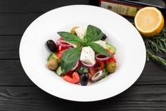 Geschmackvoller griechischer Salat mit Frischgemüse auf weißer Platte Stockfotografie