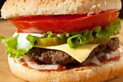 Geschmackvoller großer Cheeseburger-Abschluss oben Lizenzfreies Stockbild