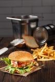 Geschmackvoller Hühnerburger mit Pommes-Frites auf Holztisch im kitche Lizenzfreie Stockfotos