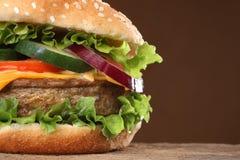 Geschmackvoller Hamburger auf hölzernem Hintergrund Lizenzfreie Stockfotos