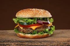 Geschmackvoller Hamburger auf hölzernem Hintergrund Stockfoto