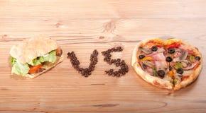 Geschmackvoller Hamburger und Pizza. vesrsus. gegen Stockfoto
