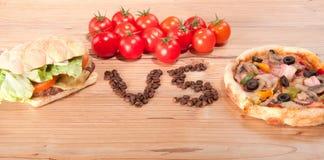 Geschmackvoller Hamburger und Pizza. vesrsus. gegen und einige Tomaten Lizenzfreies Stockfoto