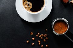 Geschmackvoller Kaffee auf der schwarzen Tabelle mit Schokolade lizenzfreie stockfotos