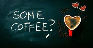 Geschmackvoller Kaffee-Espresso in einer Herz-Form-roten Schale auf einer Tafel Stockbild