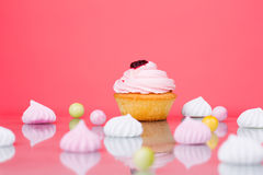 Geschmackvoller kleiner Kuchen auf dem korallenroten Hintergrund Stockfotografie