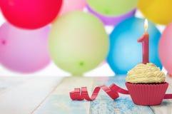 Geschmackvoller kleiner Kuchen und Geburtstagskerze Stockfoto