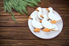 Geschmackvoller Lebkuchen saugen geformte Plätzchen auf einer Platte mit dem Ohr des Weizens auf einem hölzernen Hintergrund Stockfoto