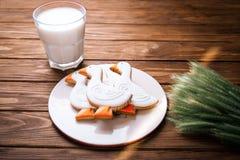 Geschmackvoller Lebkuchen saugen geformte Plätzchen auf einer Platte mit Glas Milch und mit dem Ohr des Weizens auf einem hölzern Lizenzfreie Stockbilder