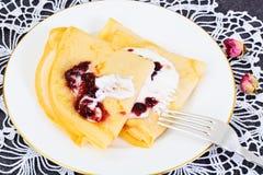 Geschmackvoller Pfannkuchen-Stapel mit Sahne und Stau Stockfotografie