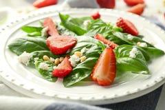 Geschmackvoller Salat mit Spinat und Erdbeere auf Platte Lizenzfreie Stockfotografie