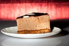 Geschmackvoller Schokoladenkuchen auf redbackground Stockbilder