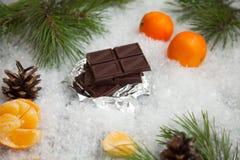 Geschmackvoller Schokoriegel mit Mandarinen auf einem schneebedeckten Hintergrund Lizenzfreies Stockbild