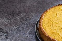 Geschmackvoller selbst gemachter Zitronenkäsekuchen des strengen Vegetariers auf dunkelgrauer Steinplatte stockfotografie