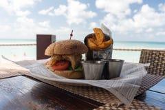 Geschmackvoller Spezialistenburger mit Kartoffelkeilen lizenzfreie stockbilder