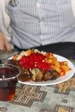 Geschmackvolles Abendessen auf dem Tisch und Plastikglas Tee Stockbilder