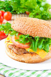 Geschmackvolles amerikanisches Mittagessen - Cheeseburger mit Fleischkotelett, Käse und Lizenzfreie Stockfotografie