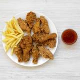 Geschmackvolles Fastfood: gebratenes Hühnerbeine, würzige Flügel, Pommes-Frites, Hühnerstreifen und sauer-süße Soße auf weißer Pl stockbilder