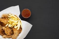 Geschmackvolles Fastfood: gebratenes Hühnerbeine, würzige Flügel, Pommes-Frites und Hühnerstreifen im Papierkasten, sauer-süße So stockbild