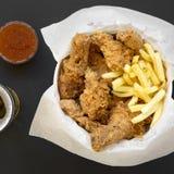 Geschmackvolles Fastfood: gebratenes Hühnertrommelstöcke, würzige Flügel, Pommes-Frites und Hühnerfinger im Papierkasten, sauer-s stockfotografie