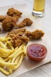 Geschmackvolles Fastfood: gebratenes Hühnertrommelstöcke, würzige Flügel, Pommes-Frites und Hühnerstreifen mit sauer-süßer Soße u stockfotografie