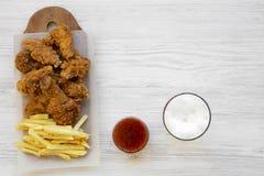 Geschmackvolles Fastfood: gebratenes H?hnertrommelst?cke, w?rzige Fl?gel, Pommes-Frites und H?hnerfinger, kaltes Bier und sauer-s lizenzfreie stockfotos