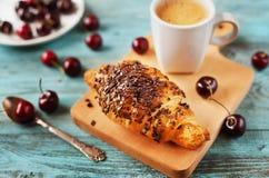 Geschmackvolles Frühstück mit frischem Hörnchen, Kaffee und Kirschen auf einem Holztisch Stockfotografie