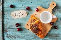 Geschmackvolles Frühstück mit frischem Hörnchen, leerem Tasse Kaffee, Kirschen und Anmerkungen über einen Holztisch Stockbild