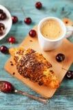 Geschmackvolles Frühstück mit frischem Hörnchen, Kaffee und Kirschen auf einem Holztisch Stockbild
