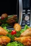 Geschmackvolles geräuchertes Huhn mit Gemüse und Kräutern gegen einen Hintergrund eines Mikrowellenherds stockbilder