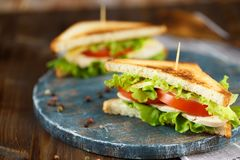 Geschmackvolles Sandwich zwei mit Huhn, Tomaten, Kopfsalat, Käse auf einer hölzernen Platte auf einem dunklen Hintergrund lizenzfreie stockfotos