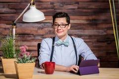 Geschmeichelte Frau am Schreibtisch Stockbild