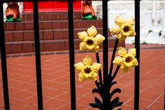 Geschmiedete gelbe Einzelteile auf Tor Dekoratives Fragment in Form einer Blume Asphaltieren Sie Tordekorationen mit hellen Blume lizenzfreie stockfotos