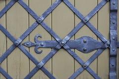 Geschmiedete Stahlbänder, die einen Diamanten auf einem Holzfuß, Hintergrund, Beschaffenheit bilden Lizenzfreie Stockfotos