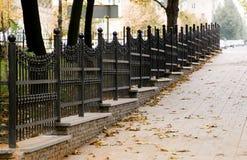 Geschmiedeter Zaun in der Herbststraße Stockbilder
