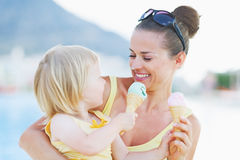Geschmierte Mutter und Baby, die Eiscreme isst Lizenzfreie Stockfotos