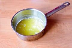Geschmolzene Butter in einem Metalltopf auf einem Holztisch lizenzfreie stockbilder
