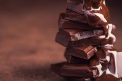 geschmolzene Schokolade, die in ein Stück Schokoriegel gießt lizenzfreie stockbilder