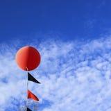 Geschnürter roter Ballon im Himmel lizenzfreie stockfotografie