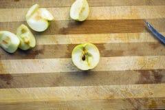 Geschnittene Äpfel auf alter benutzter hölzerner Küche verschalen stockbild