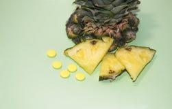 Geschnittene Ananas und Pillen auf einem blauen Hintergrund Gesundheit und natürliche Vitamine lizenzfreie stockfotos