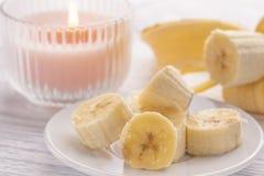 Geschnittene Banane auf einer weißen Platte und einem hellen Holztisch Rosa brennende Kerze in der Nähe stockfotos